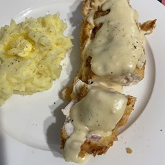 White plate containing mashed potato with a dollop of butter, chicken cordon bleu with dijon sauce.